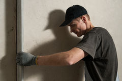 Woker fixes a guide to align the walls with stucco Stock Images