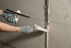 Woker fixes a guide to align the walls with stucco Stock Photos