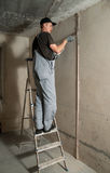 Woker fixes a guide to align the walls with stucco Royalty Free Stock Photo