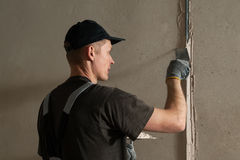Woker fixes a guide to align the walls with stucco Royalty Free Stock Photos