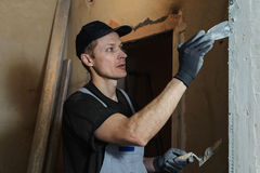 Woker fixes a guide to align the walls with stucco Stock Photography