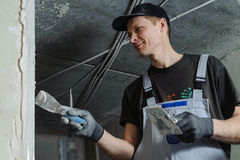 Woker fixes a guide to align the walls with stucco Stock Photo