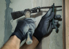 Woker hammers a nail with a foot into a wall Stock Photography