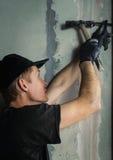 Woker martèle un clou avec un pied dans un mur image stock