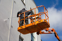 Woker in platform wash a building. Woker in the orange cherry-picker platform wash a building Royalty Free Stock Image