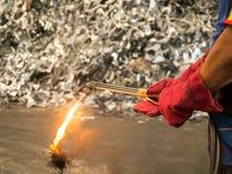 Woker que sostiene la antorcha para corte de metales con hollín y la llama adentro reciclan la fábrica imagenes de archivo