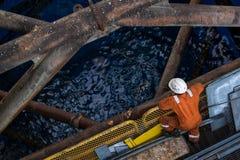 Wokers a solleva sulla gamba con il crick dell'impianto offshore Immagini Stock Libere da Diritti