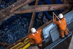 Wokers a solleva sulla gamba con il crick dell'impianto offshore Immagine Stock Libera da Diritti