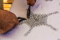 Woking on a chainmail. A man working on a medieval chainmail with old tools Stock Images