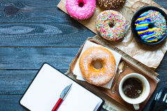 Woking Desk Table with Colorful Donuts breakfast composition stock photo