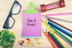 Hourglass, pencils, eyeglass and Take a break word written on notepad. Woking table with hourglass, pencils, eyeglass and Take a break word written on notepad royalty free stock photo