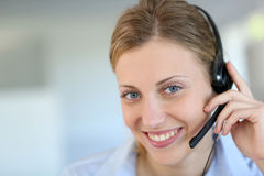 Wokirng girl with headset in customer service. Closeup of attractive blond customer service assistant Stock Images