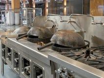 Woks έτοιμο να μαγειρεψει στην αναμμένη βιομηχανική κουζίνα στοκ φωτογραφία