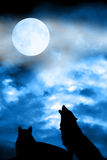 Wolf couple howling to moon. Couple of wolves silhouettes with full moon in the sky Stock Photo