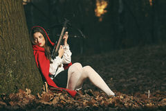 Wolf hunter. Little red riding hood leaning to a tree in the forest with a crossbow. Wolf hunter royalty free stock image
