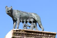 She-wolf nursing twins while founders of Rome with blue sky back Royalty Free Stock Photo
