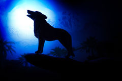 Wolf in silhouette howling to the full moon Royalty Free Stock Image
