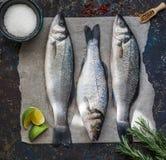 Wolfsbarsch mit drei rohen Fischen und andere Bestandteile auf dunklem Weinlesehintergrund Stockbilder