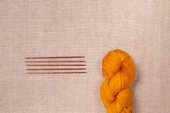 Wolgaren van oranje kleur met houten breinaalden Stock Afbeeldingen