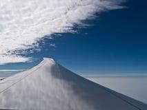 Wolk en hemelbezinning over vleugel stock foto