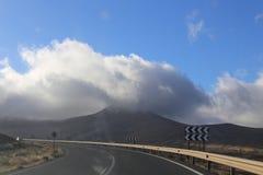 Wolken über Berg und Landstraße Lizenzfreie Stockfotos