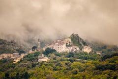 Wolken über Bergdorf von Speloncato in Korsika lizenzfreie stockfotografie