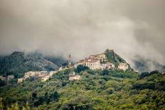 Wolken über Bergdorf von Speloncato in Korsika stockfoto