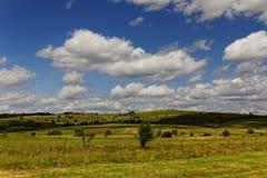Wolken über dem Feld an einem sonnigen Tag Stockfoto