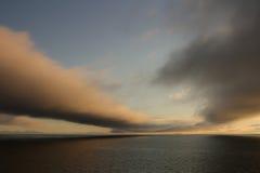 Wolken über dem Meer bei Sonnenuntergang lizenzfreie stockbilder