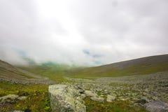 Wolken über den Bergen und dem Flussstein Stockfotos