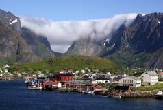 Wolken über Dorf auf Lofoten Inseln Stockbild
