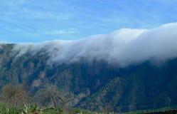 Wolken über einer Gebirgskette Stockbild