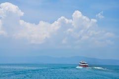 Wolken über Meer und Boot Stockfotos