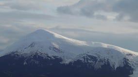 Wolken über schneebedeckten Bergen Wolken bewegen sich nah an der Gebirgsspitze stock footage