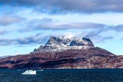 Wolken über Sermitsiaq-Bergspitzen umfasst im Schnee mit Blau Lizenzfreie Stockfotos
