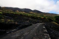 Wolken über Straße vorbei durch einen Vulkanberg Lizenzfreie Stockfotografie