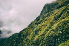Wolken achter een groene rotsachtige berg Stock Afbeelding
