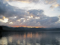 Wolken bei Sonnenaufgang über See lizenzfreie stockfotografie