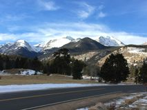 Wolken über Schnee mit einer Kappe bedeckten Bergspitzen und Straße Lizenzfreie Stockfotografie
