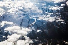 Wolken in bergen met sneeuw op kant Stock Afbeeldingen