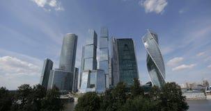 Wolken bewegen sich über Geschäftszentrumwolkenkratzer Moskaus internationale Timelapse Flugzeugblattspur im Himmel oben