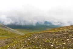 Wolken boven de bergen en de helling Stock Afbeelding