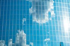 Wolken dachten über Glasfassadenwand des Gebäudes nach Bewölkte Reflexion des blauen Himmels in den Fenstern Moderne Glasarchitek Lizenzfreie Stockfotos