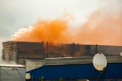 Wolken des orange Rauches von der schweren industriellen Eisenanlage, viel Rauch von der metallurgischen Anlage, Umweltprobleme,  Lizenzfreies Stockfoto