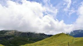 Wolken, die in alpines Tal gegen Berge und Himmelstation sich bewegen stock footage