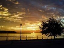 Wolken, die bei Sonnenaufgang über Wasser brechen Stockfoto