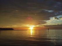 Wolken, die bei Sonnenaufgang über Wasser brechen Stockbilder