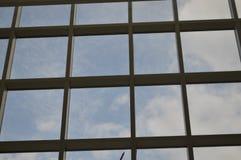 Wolken, die in den Glasfenstern sich reflektieren Stockbild