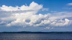 Wolken, die in den Himmel über dem See schwimmen Lizenzfreie Stockfotografie