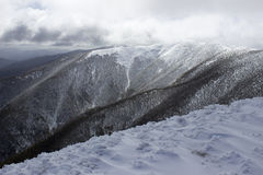 Wolken die over sneeuw afgedekte berg opdoemen Stock Foto